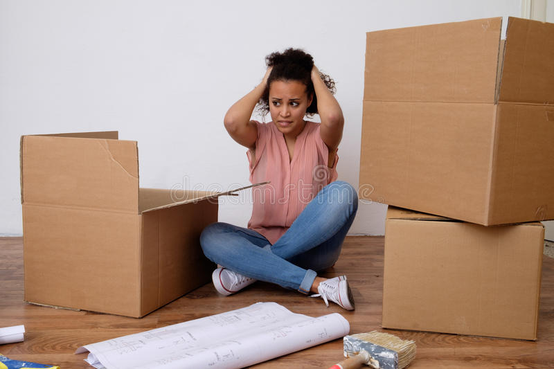 Desperate and tired woman during home relocation stock photography