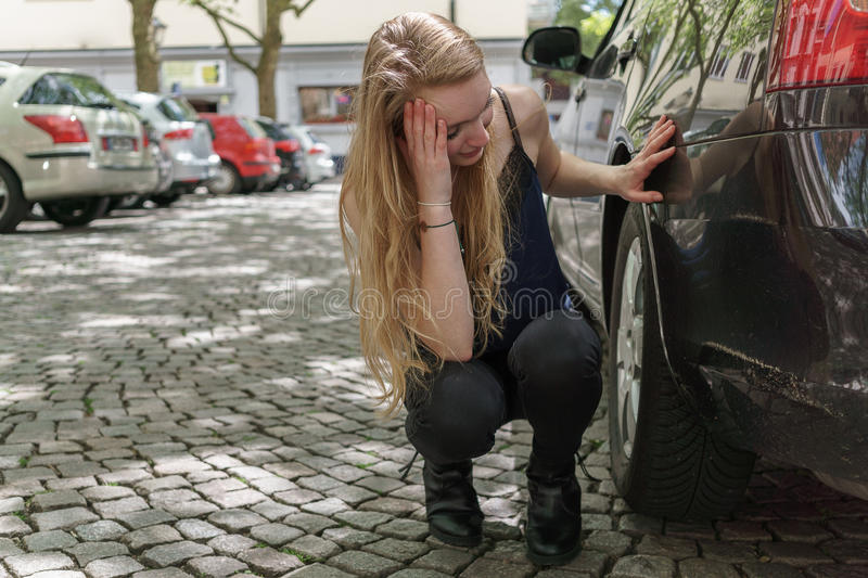 Desperate woman checking the damage to her car. Desperate young woman checking the damage to her car following a motor vehicle accident crouching down looking at stock image