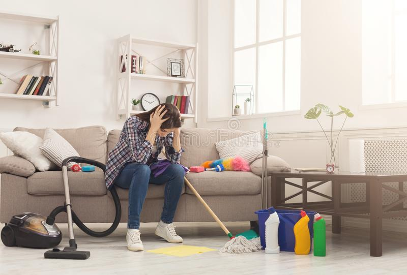 Desperate woman cleaning house with lots of tools. Young tired girl sitting on couch and holding her head, surprised of detergents quantity, copy space royalty free stock photo