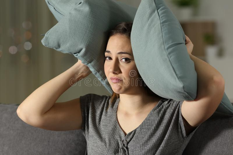 Desperate woman covering ears to protect from noise. Desperate woman covering ears to protect from neighbour noise sitting on a couch in the living room at home stock image