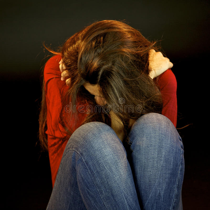 Desperate woman crying holding herself stock photos