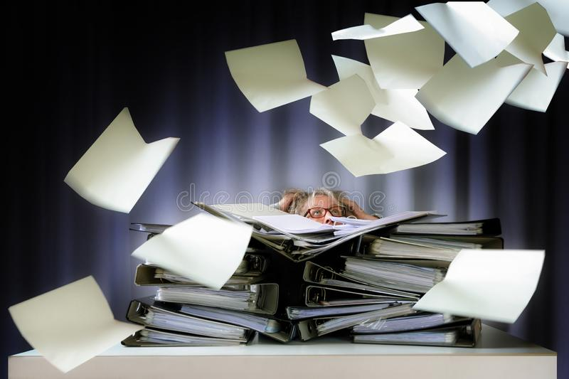 Desperate woman sinks behind stacks of ring binders on an office desk and lots of papers are flying down, concept of excessive stock photography