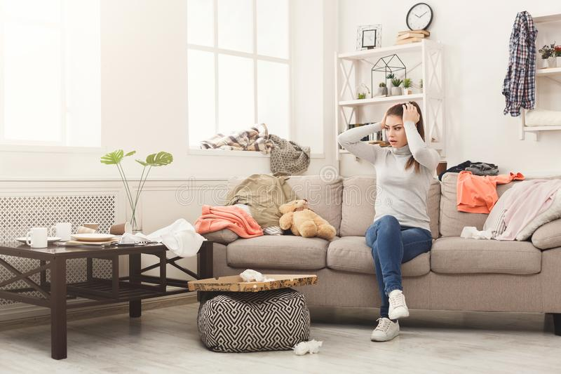 Desperate woman sitting on sofa in messy room. Desperate helpless woman sitting on sofa in messy living room. Young girl surrounded by many stack of clothes stock photos