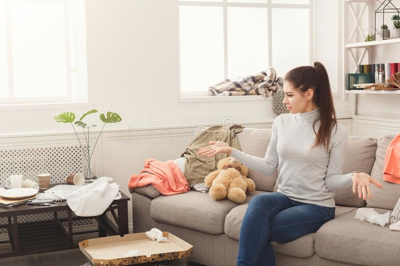 Desperate woman sitting on sofa in messy room. Desperate helpless woman sitting on sofa in messy living room. Young girl surrounded by many stack of clothes stock photography