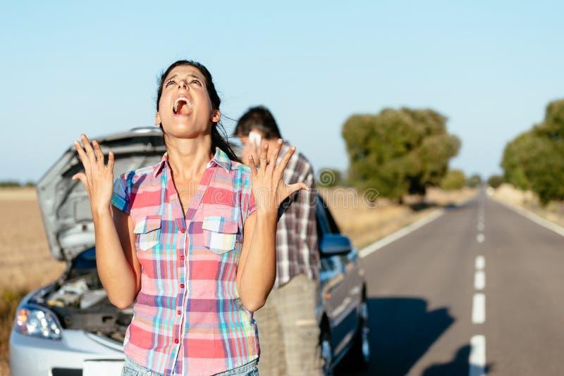 Desperate woman suffering car breakdown royalty free stock image