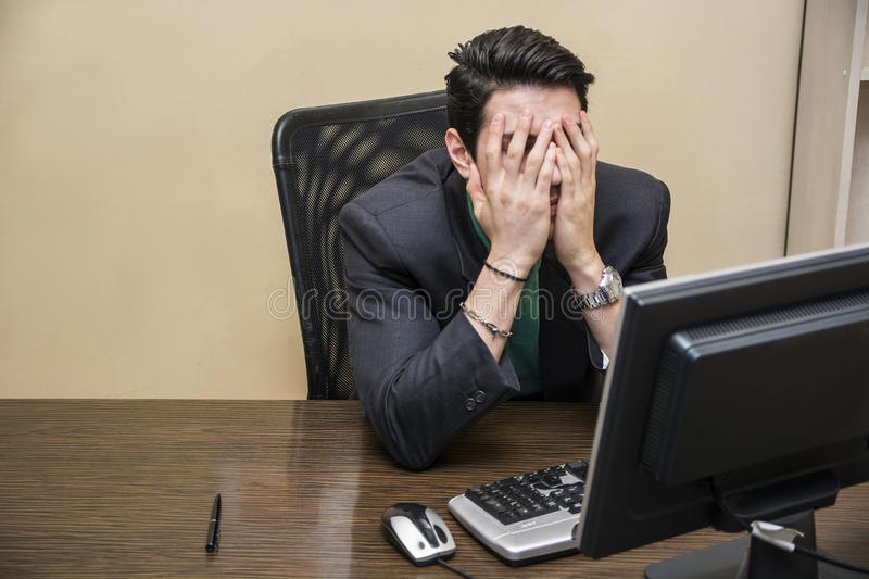 Desperate, worried young businessman sitting at his desk royalty free stock photos