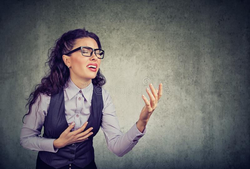 Desperate business woman asking for help. Desperate young business woman in glasses screaming asking for help forgiveness royalty free stock image