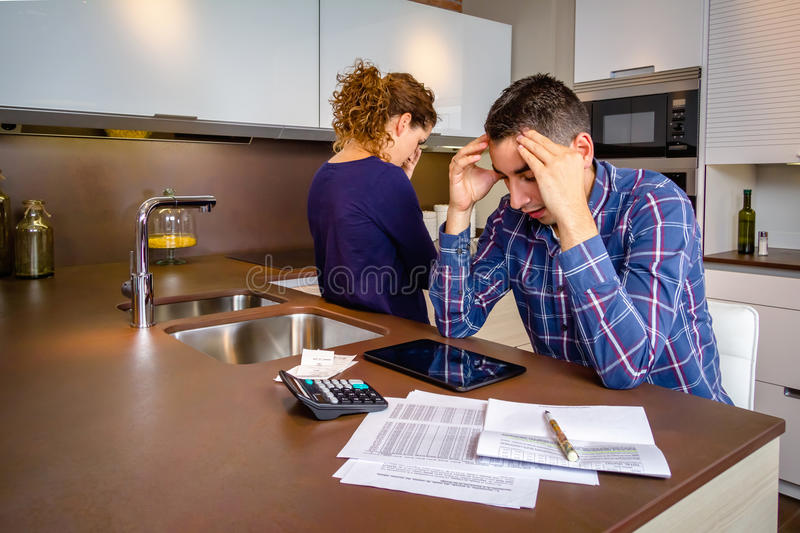 Desperate young couple with debts reviewing their stock image