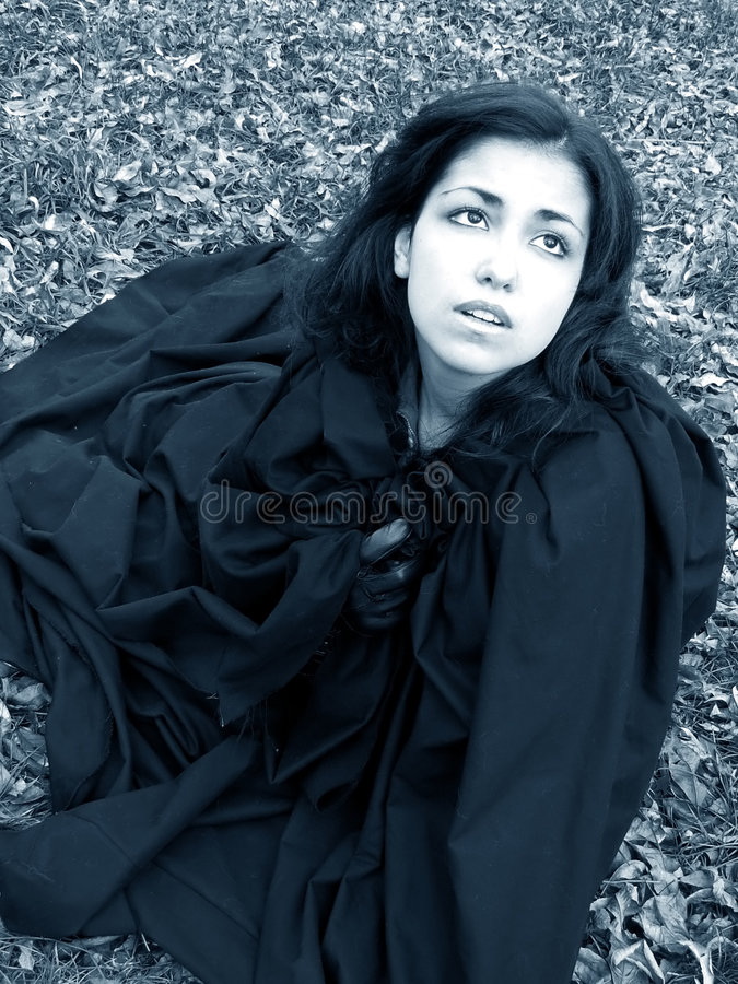 Desperation. Young woman in black cap fallen among leaves crying for help to the heavens