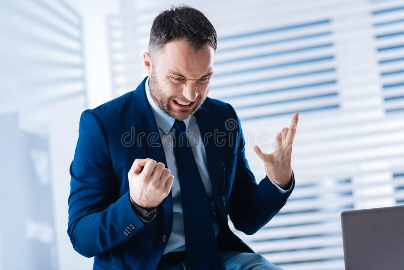 Furious young businessman having a misfortune at work and looking angry. Desperation. Expressive angry desperate businessman taking a misfortune at work too royalty free stock image
