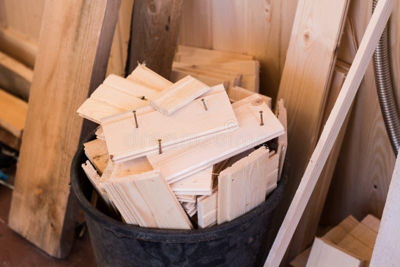 Desperdício da construção no reparo de uma casa de madeira Barras de madeira com uma cesta fotografia de stock