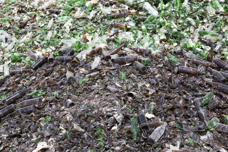 Desperdício do vidro em reciclar a facilidade Brown e frascos verdes imagens de stock
