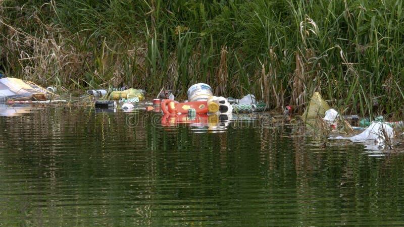 Desperdícios, latas e garrafas despejados na água imagens de stock royalty free