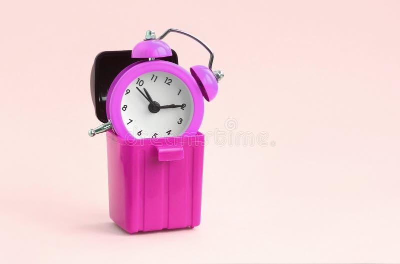 Desperdi?ando o conceito do tempo Despertador no escaninho de lixo imagem de stock