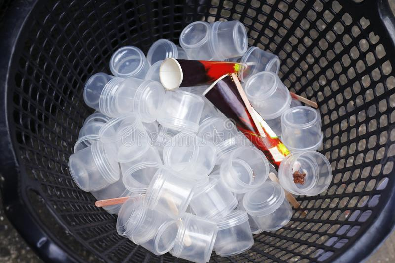 Desperdice copos plásticos muitos na cesta, lixo plástico, poluição suja, plástica de vidro plástica do lixo do desperdício na op fotos de stock royalty free