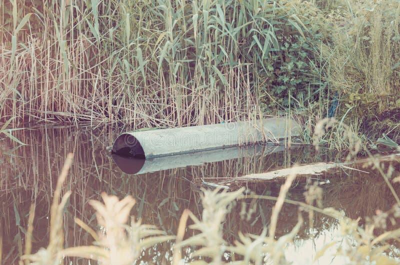 Desperdice o volume de água da tubulação de água no rio/conceito da ecologia: wat fotos de stock