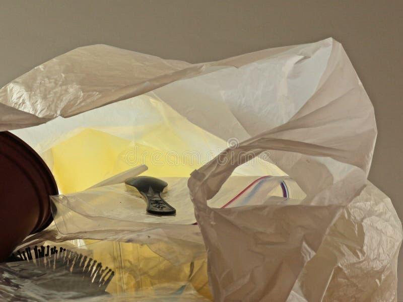 Desperdicios plásticos en el bolso de plástico transparente que miente en una superficie plana imagenes de archivo