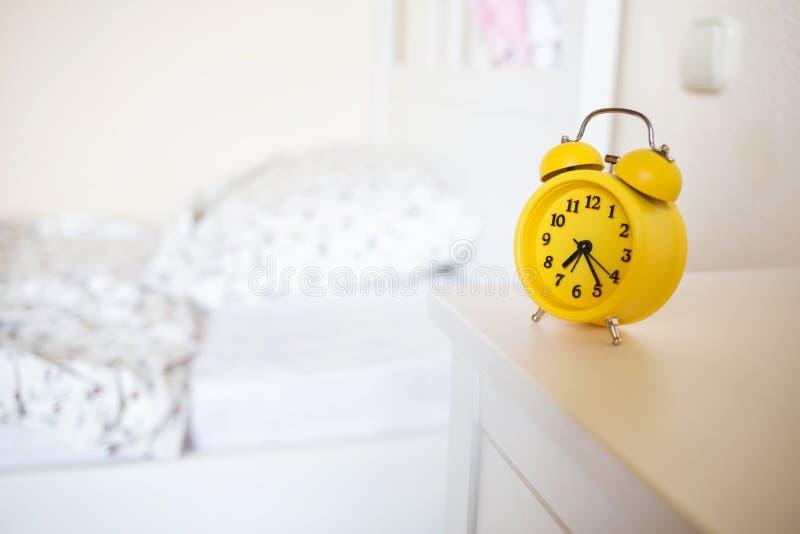 Despertador amarelo que está no nightstand no fundo da cama no interior da sala ` s da cama não feito fotografia de stock