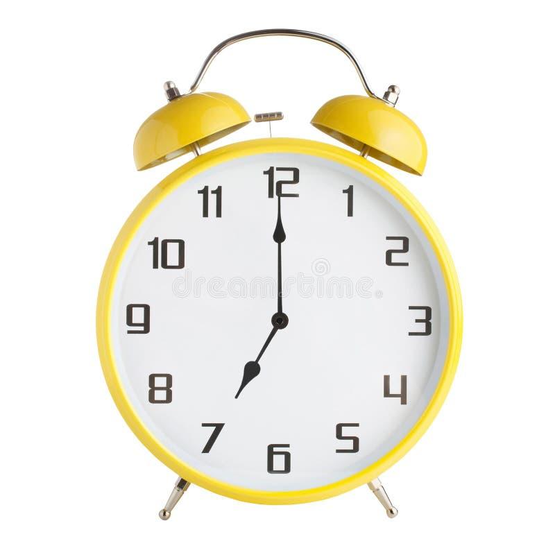 Despertador análogo amarelo que mostra sete horas isoladas no fundo branco imagem de stock royalty free