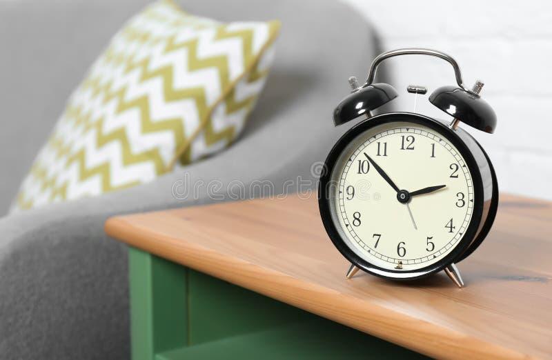 Despertador análogo en la tabla lateral en la sala de estar, espacio para el texto imágenes de archivo libres de regalías