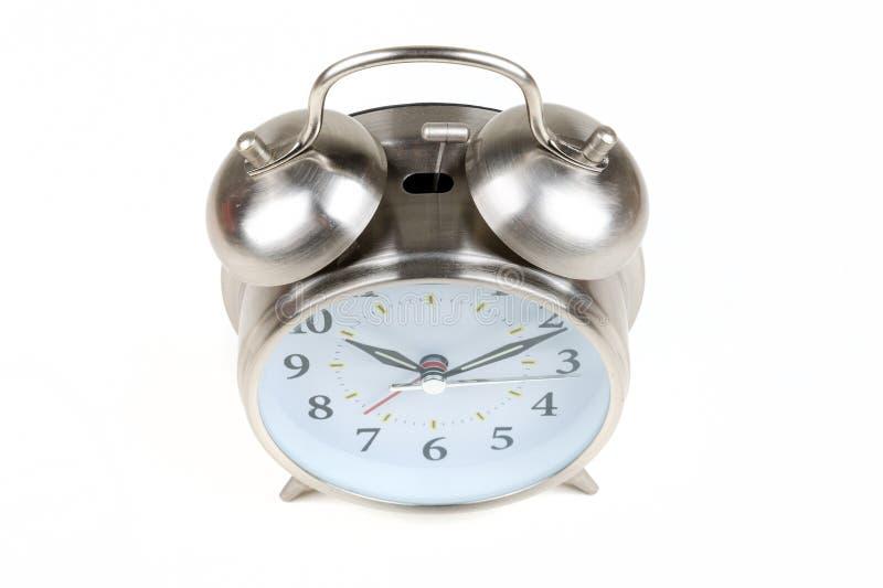 Despertador antiquado de aço inoxidável em um fundo branco fotografia de stock