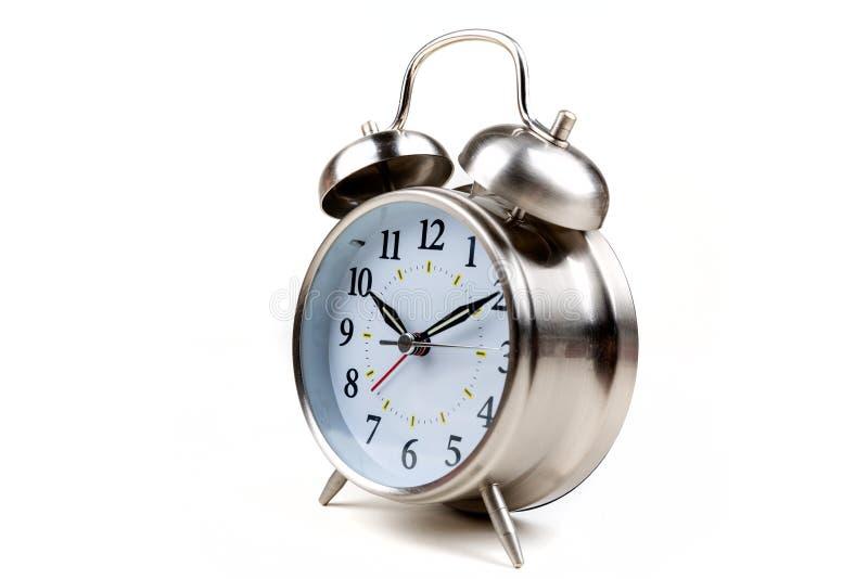 Despertador antiquado de aço inoxidável em um fundo branco fotos de stock royalty free
