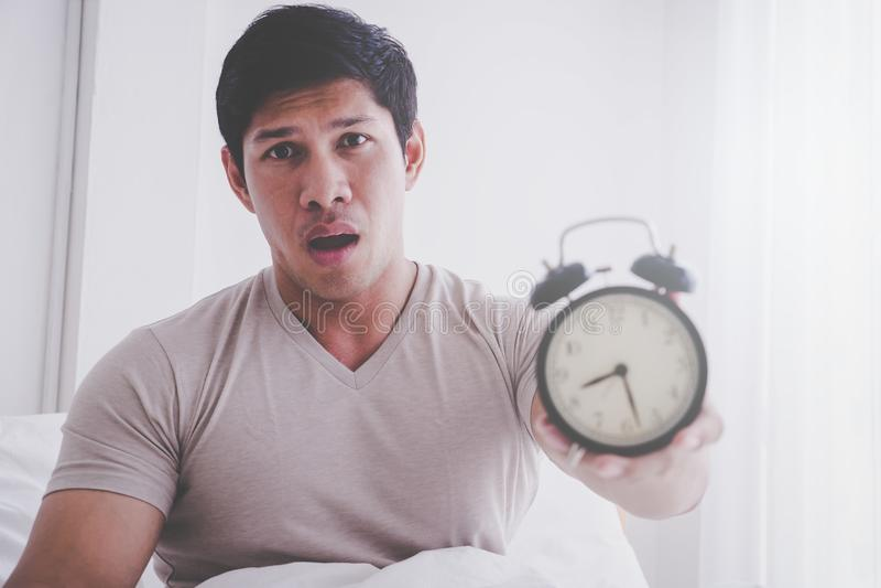 Despertador apenas levantado y chocado del hombre último imagenes de archivo