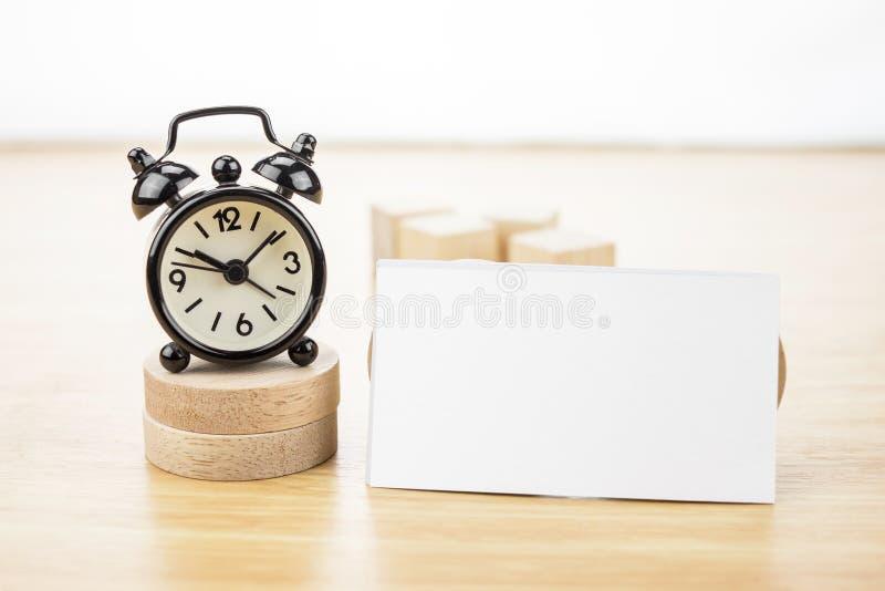 Despertador ascendente y negro de visita de la mofa en blanco de la tarjeta en woode ligero imagen de archivo libre de regalías