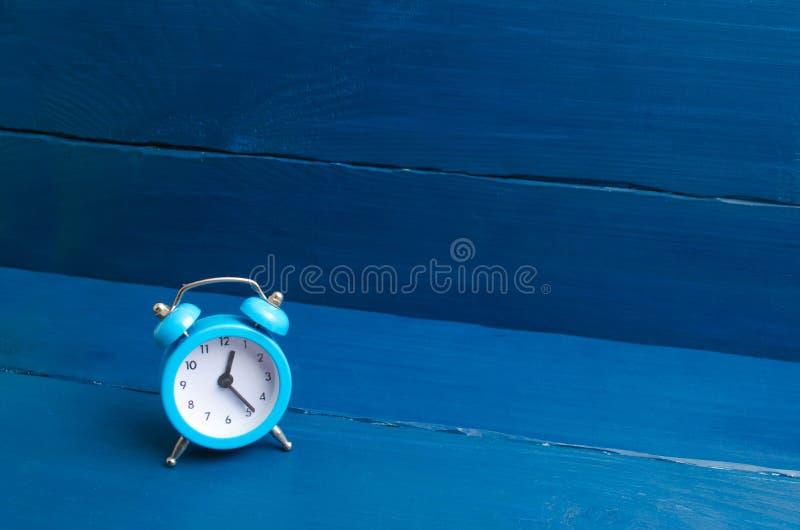 Despertador azul em um fundo de madeira azul O conceito do tempo Tradução de horas pelo inverno ou as horas de verão imagens de stock