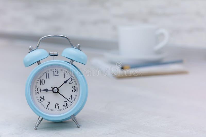 Despertador azul en luz de la mañana y la taza de café imagenes de archivo