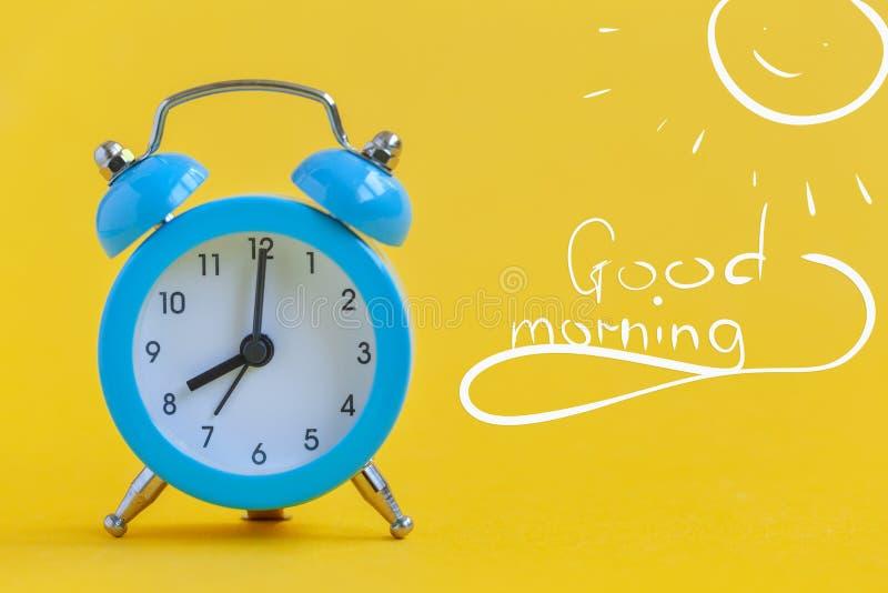 Despertador azul no fundo amarelo com bom dia do texto minimalism Contraste o conceito fotos de stock royalty free