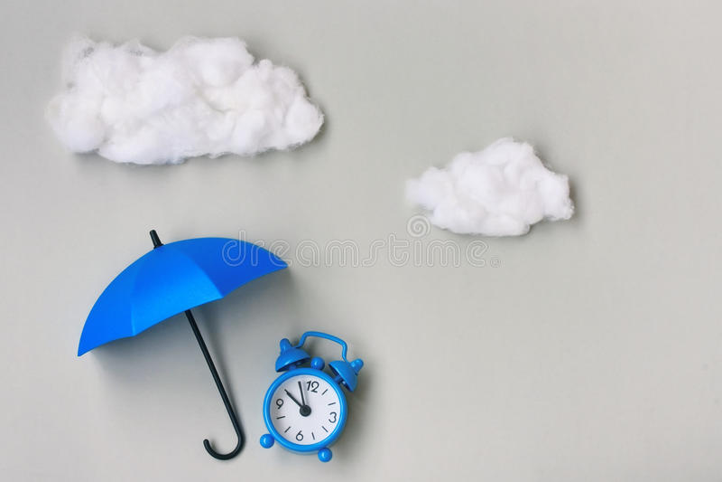 Despertador azul sob um guarda-chuva no fundo cinzento imagem de stock