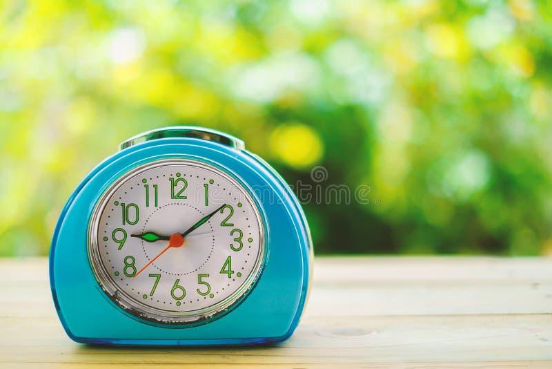 Despertador azul viejo en la tabla de madera fotografía de archivo libre de regalías