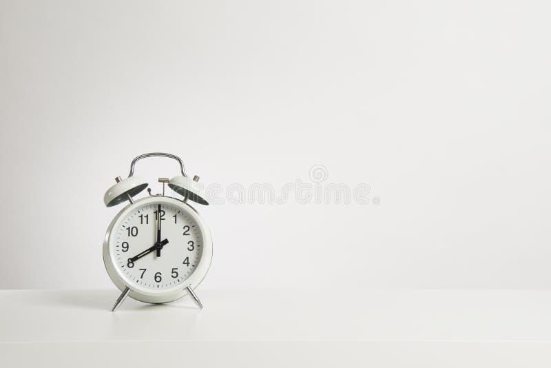 Despertador blanco del vintage en un fondo blanco del diseño con el espacio para la copia con el tiempo en las ocho imagen de archivo libre de regalías