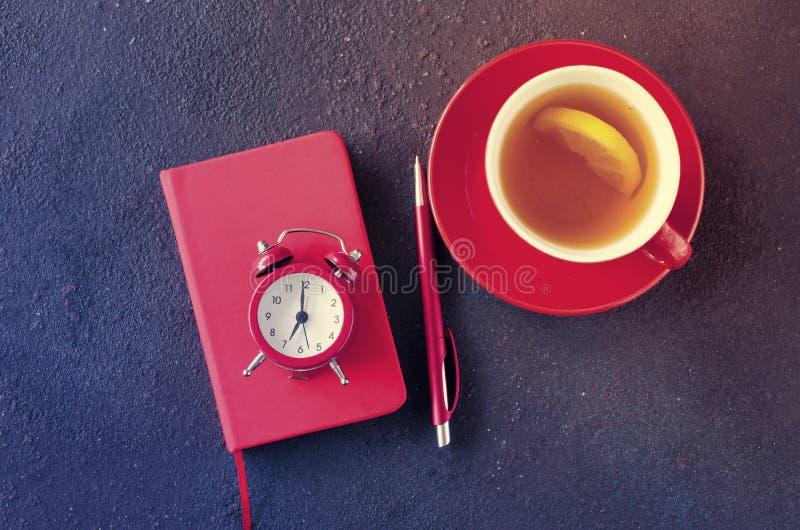 Despertador, bloco de notas, pena e copo do chá Gestão ou educação de tempo do conceito imagens de stock