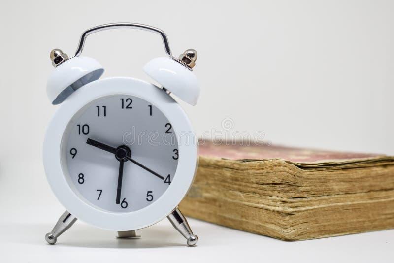 Despertador branco e livro velho ( Dictionary) no fundo branco foto de stock