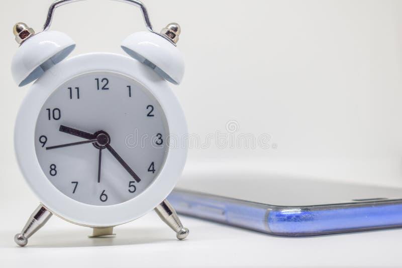 Despertador branco e telefone azul no fundo branco imagens de stock royalty free