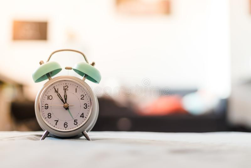 Despertador branco na cama, manhã, copyspace imagem de stock royalty free