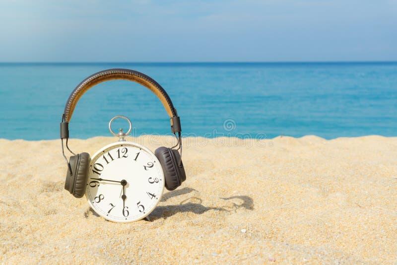 Despertador branco que veste os fones de ouvido marrons colocados na areia Mar e céu azuis como um fundo Conceito para o abrandam fotografia de stock