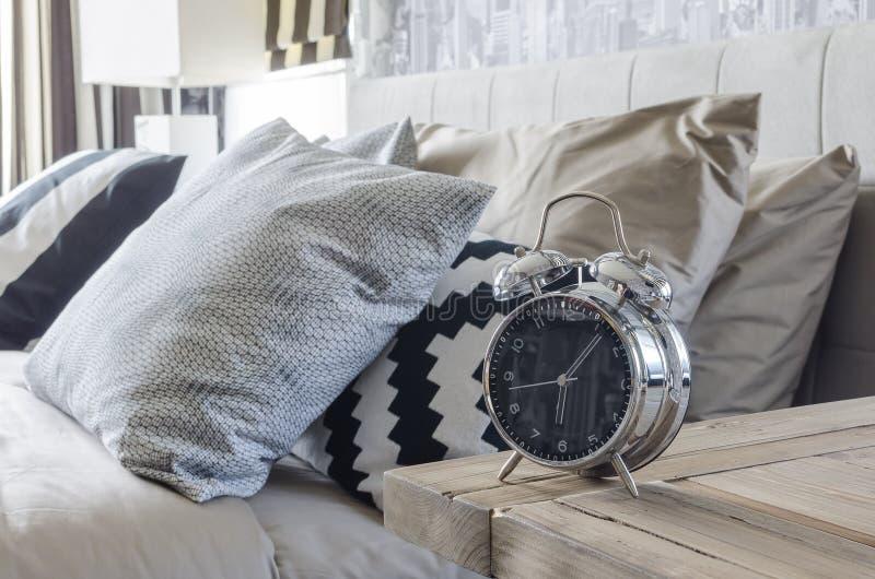 Despertador clásico del estilo en la tabla de madera en dormitorio fotografía de archivo