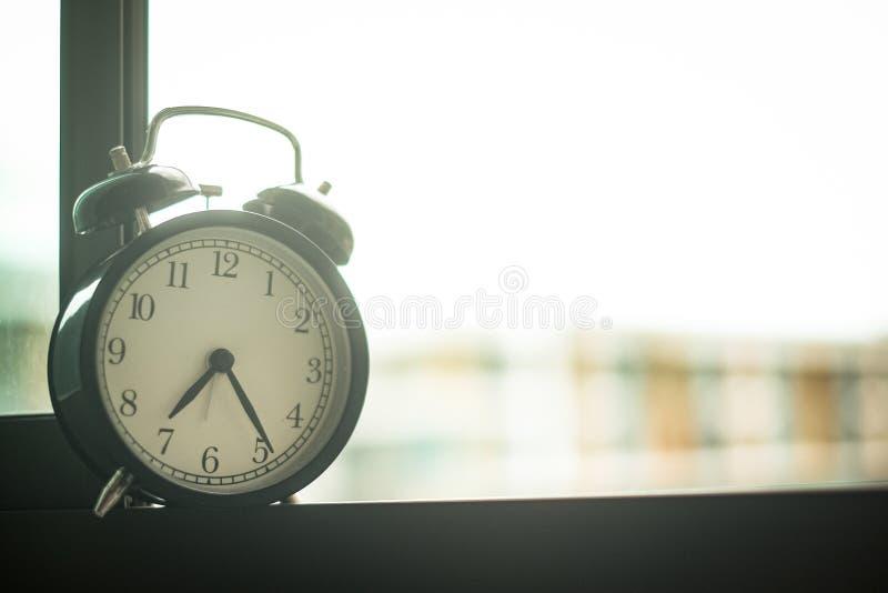 Despertador clásico en la ventana fotografía de archivo libre de regalías