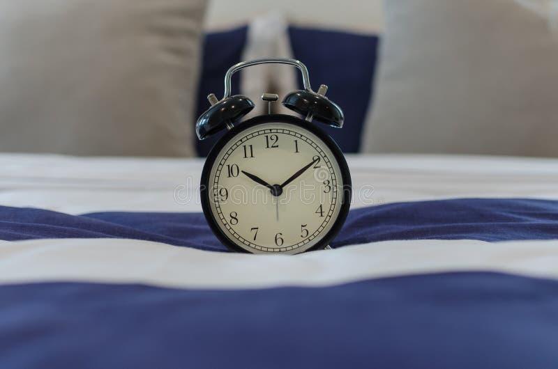 Despertador clásico negro en cama imagenes de archivo