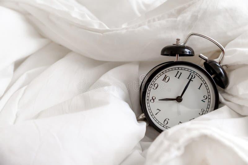 Despertador cl?ssico na cama, conceito da rotina da manh? foto de stock