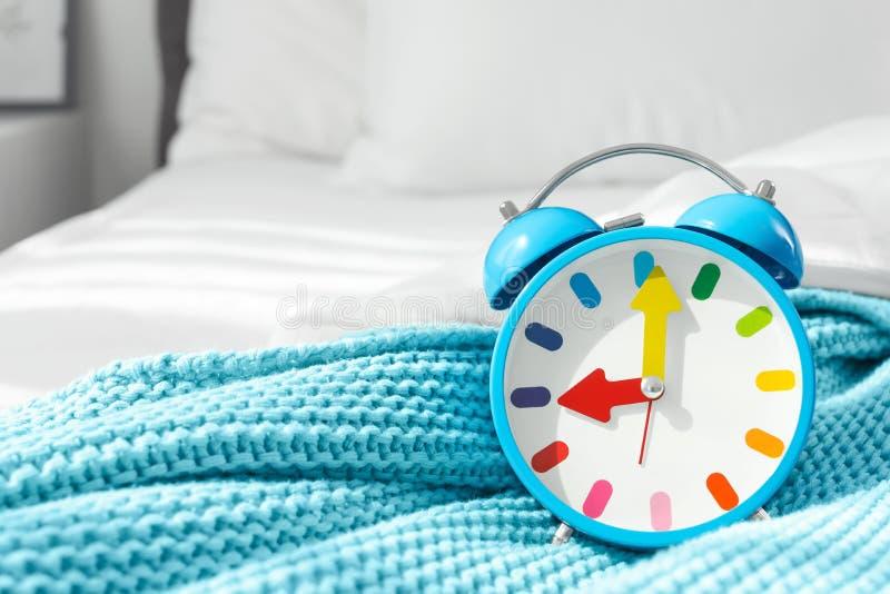 Despertador colorido en cama fotografía de archivo