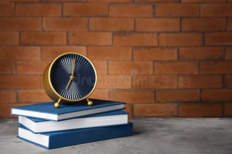 Despertador com os livros na tabela contra o fundo do tijolo Conceito da gest?o de tempo fotografia de stock royalty free