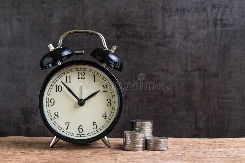 Despertador com a pilha do dinheiro de moedas na tabela de madeira e no preto fotos de stock royalty free