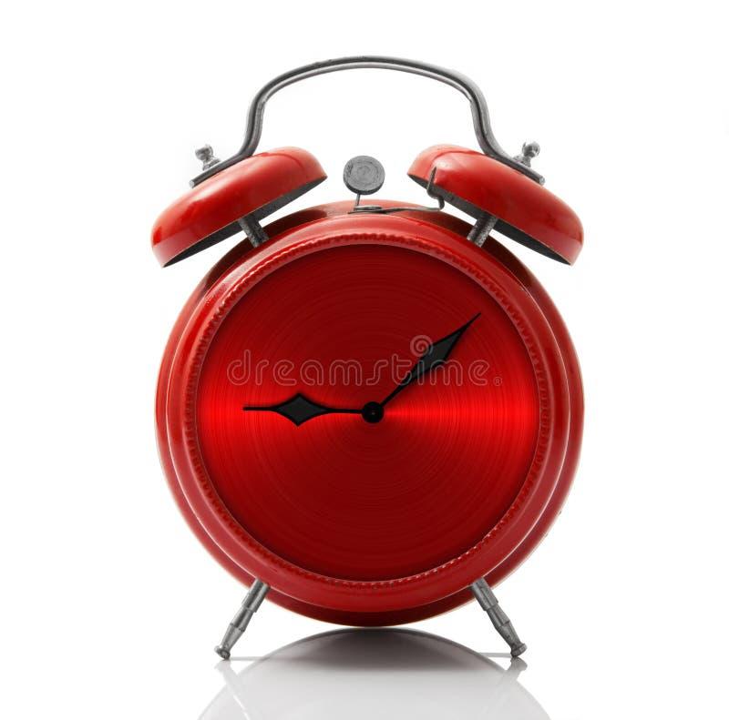 Despertador con el dial rojo del metal en el fondo blanco foto de archivo