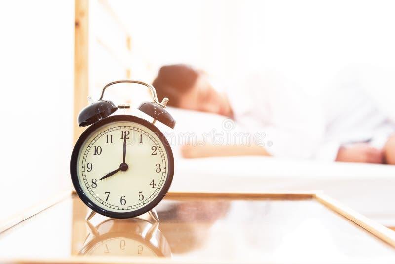 Despertador con la mujer durmiente en sitio de la cama Tiempo perezoso en concepto del d?a de fiesta fotos de archivo libres de regalías