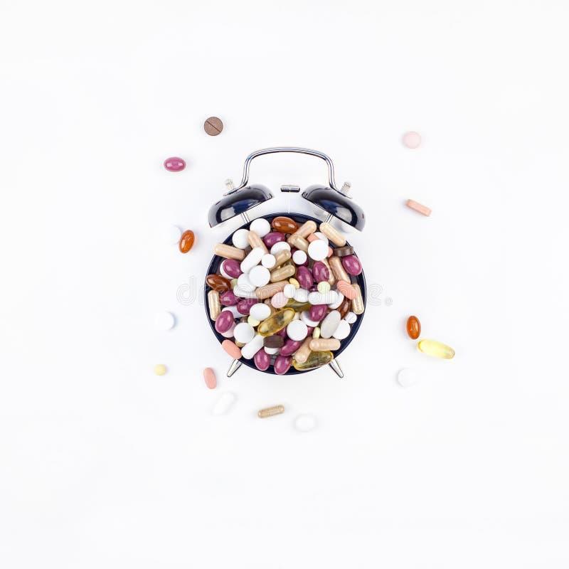 Despertador con las píldoras del color fotografía de archivo libre de regalías