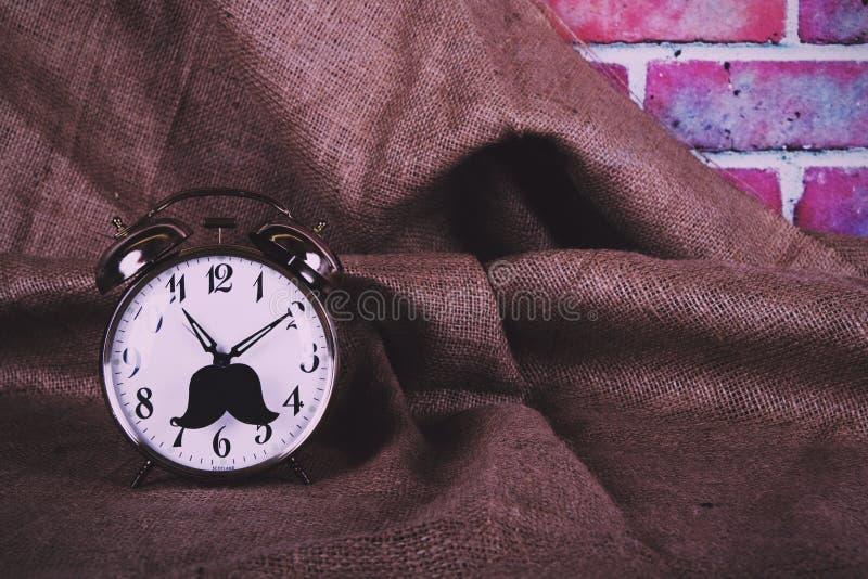 Despertador con un filtro retro del inconformista del vintage negro del bigote imagen de archivo libre de regalías